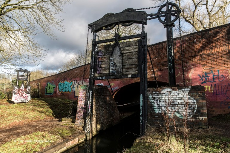 A graffiti covered guillotine lock on the North Stratford Canal.