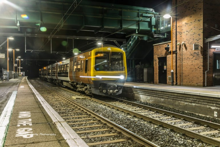 Alvechurch Station at night with a train having just stopped on the opposite platform.