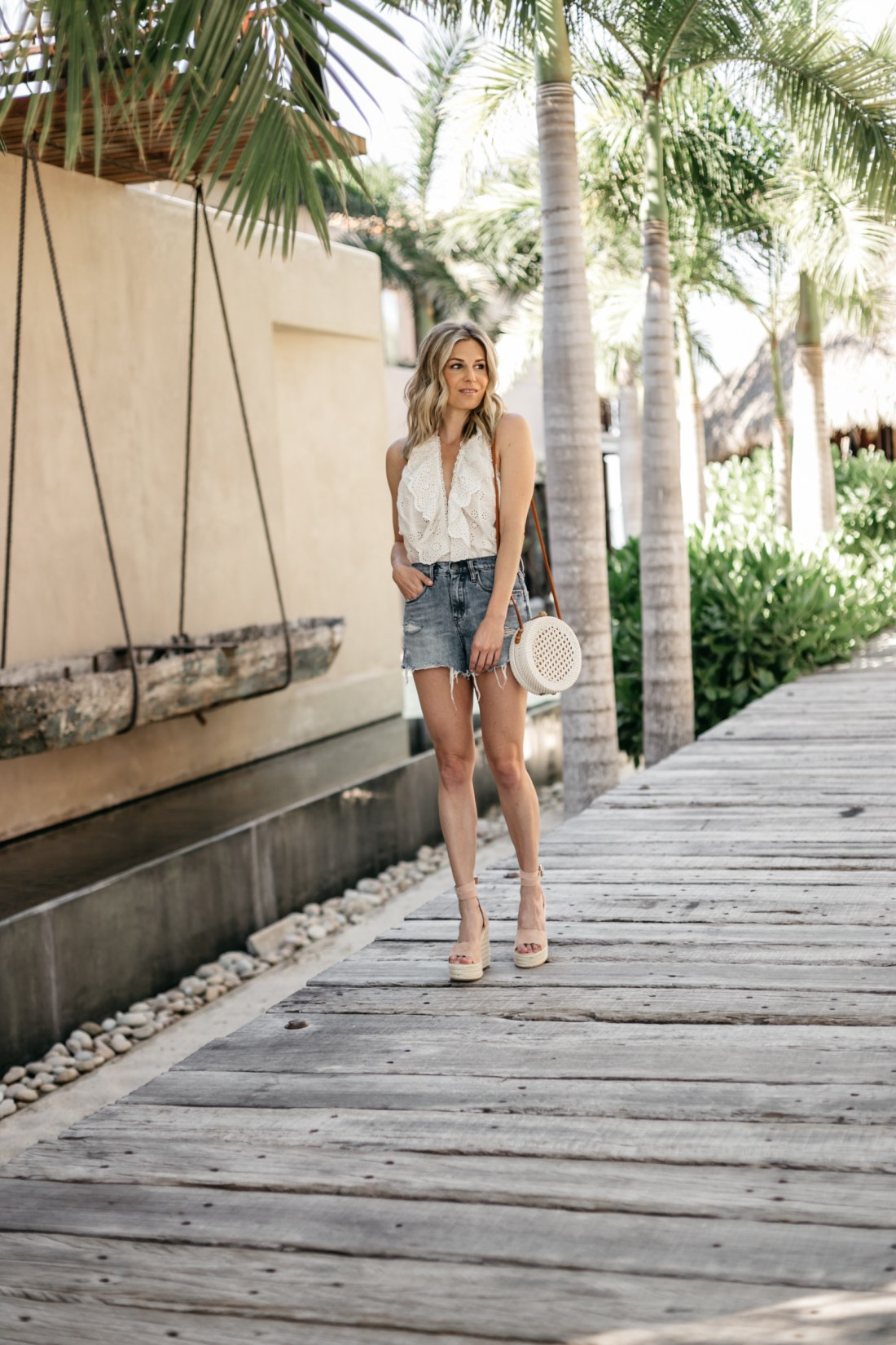 Brooke is wearing a White Ruffle Body Suit // Jean Shorts // Tan Wedges // Circle Rattan Bag