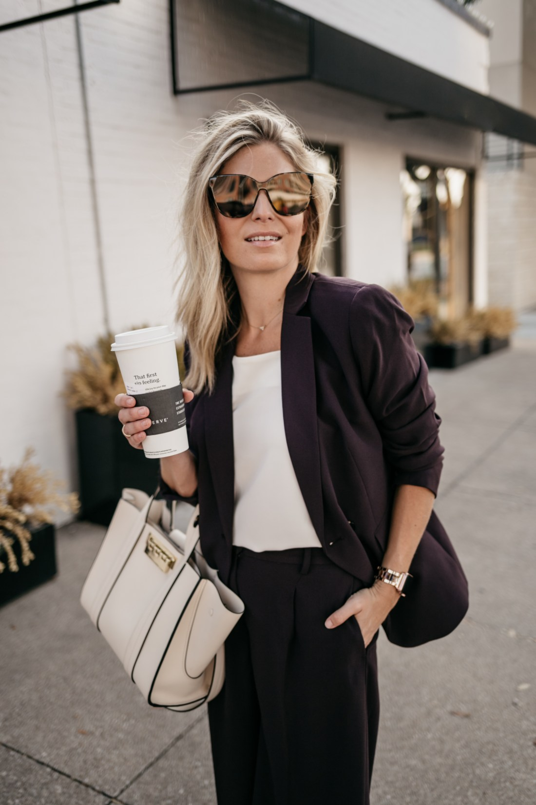 a plum blazer and a white purse