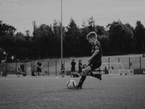 kicking ball at youth football tournament