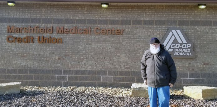 Board member John Dean in front of MMCCU building