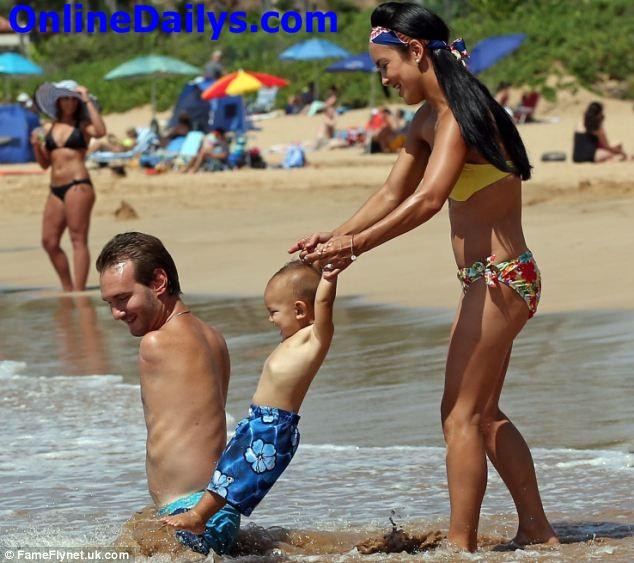 Kanae swings Kiyoshi in the waters as Nick looks on