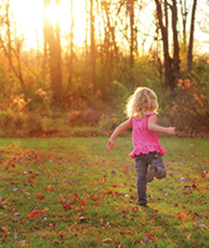 A little girl runs in a field.