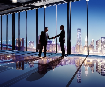 Multi-Ethnic Businessmen Shaking Hands Indoors With City As A Background