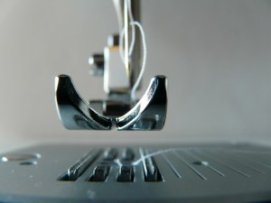 a sewing machine presser foot raised with white thread