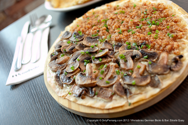 The traditional Alsatian 'Flammkuchen' made with thin crust dough, sour cream, roasted onion with topping of Mushroom and Bacon, Price: RM32++ (Choice of any half)