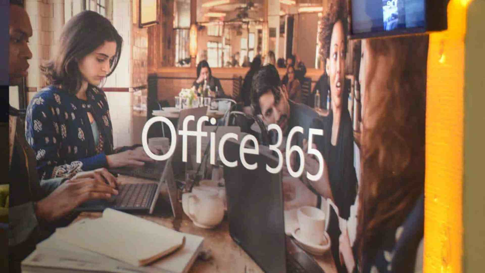 "Image of reflection on glass showing people working with Microsoft devices with ""Office 365"" text"