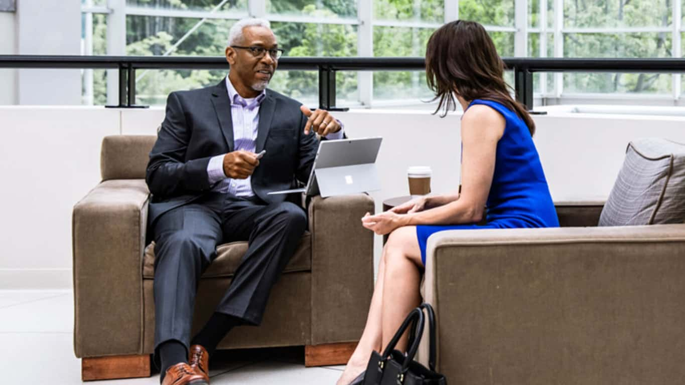 A businessman and woman with a Surface Pro