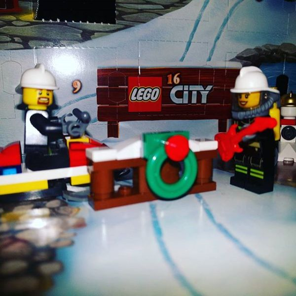 #legocityadvent Day 7: fireman & rocking fire girl are not entirely sure what has arrived today....wreath on a fence?