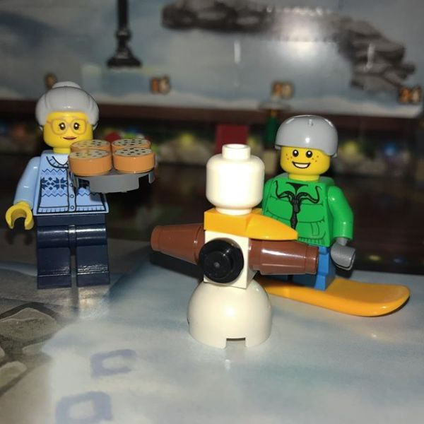 Snowboard boy showing pizza Granny the snowman he has built in #legocityadvent