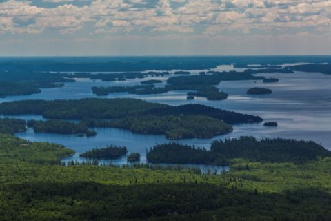 An areal view of a lake land with scattered forested islands