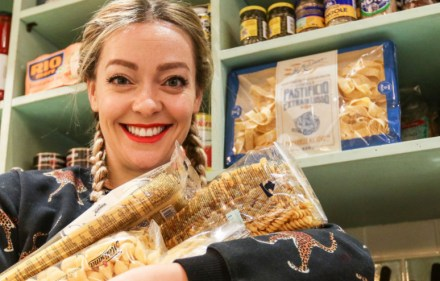 Cherry Healey holding different varieties of pasta.