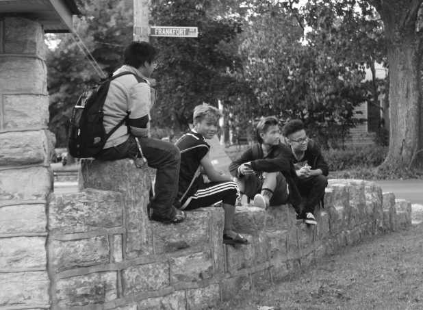 Observing the Crescent Hill Baptist Church youth group playing elbow tag, four of the youth gather on a wall and laugh. Photo By Sam Sims.