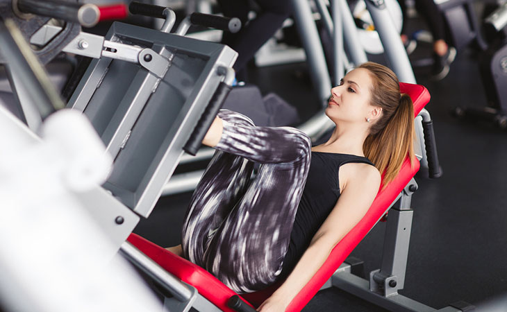 Woman Working Out In Leg Press Machine