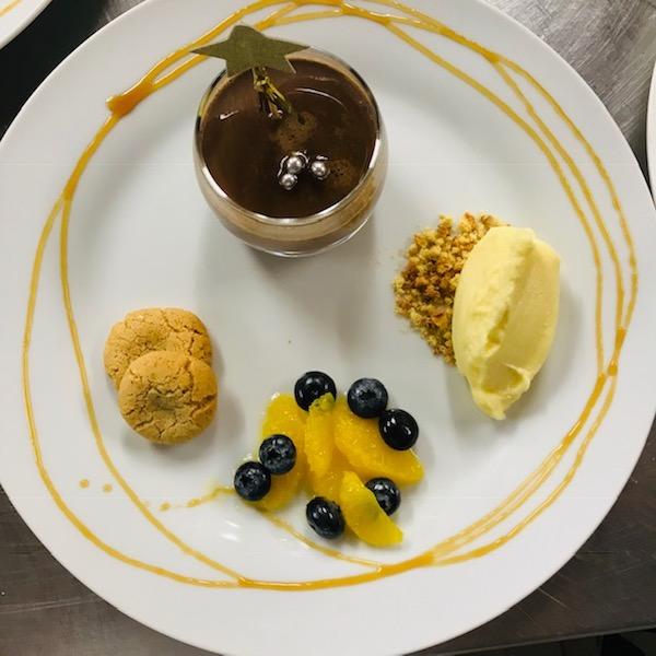 Grand dessert met chocolade panna cotta, vers fruit en sorbet van citrusfruit