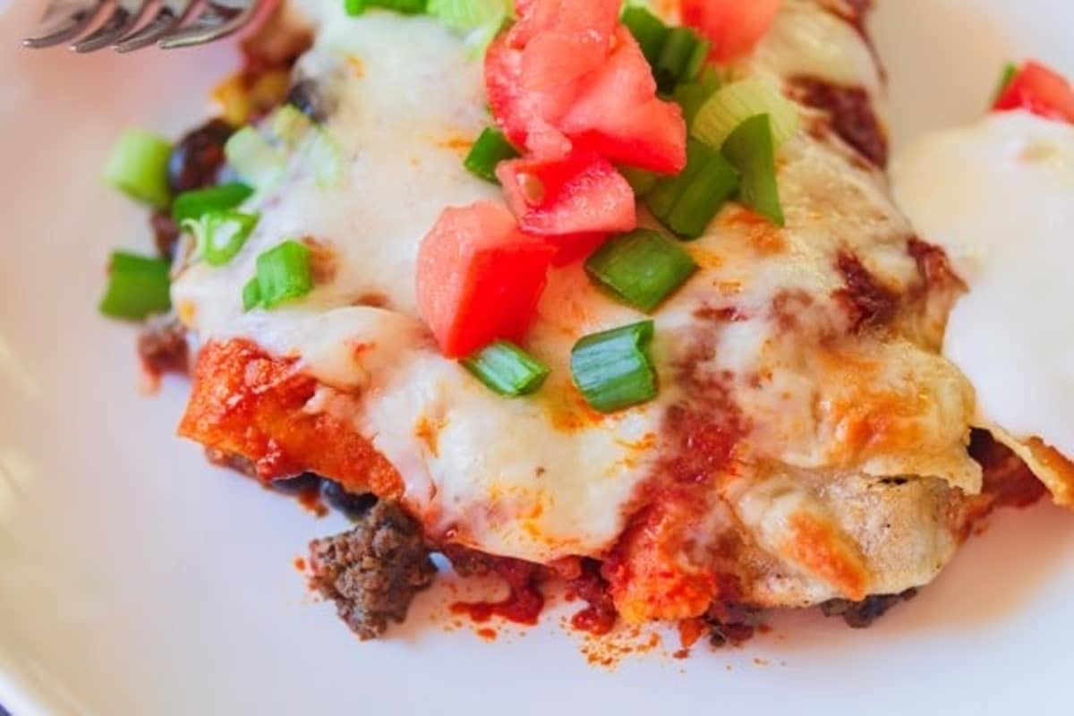 enchiladas on a plate with sour cream