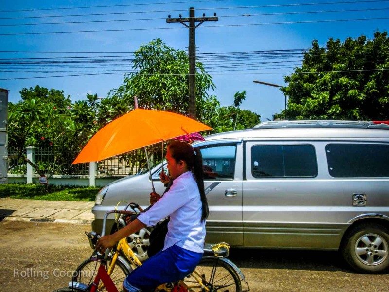 Laotian girl using Sun Umbrella on Bicycle in Vang Vieng Laos Rolling Coconut Ooaworld Photo Ooaworld