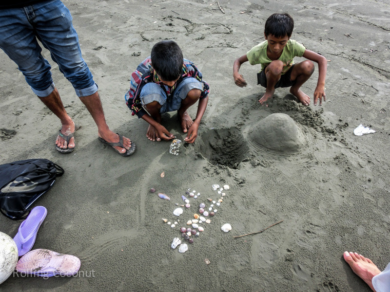 Bangladesh Cox's Bazar Playing at the beach with shells and Local Kids ooaworld Rolling Coconut Photo Ooaworld
