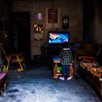 A boy watching TV in his living room, near Yangshuo China