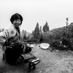 A woman sells postcards by Longsheng's rice terraces