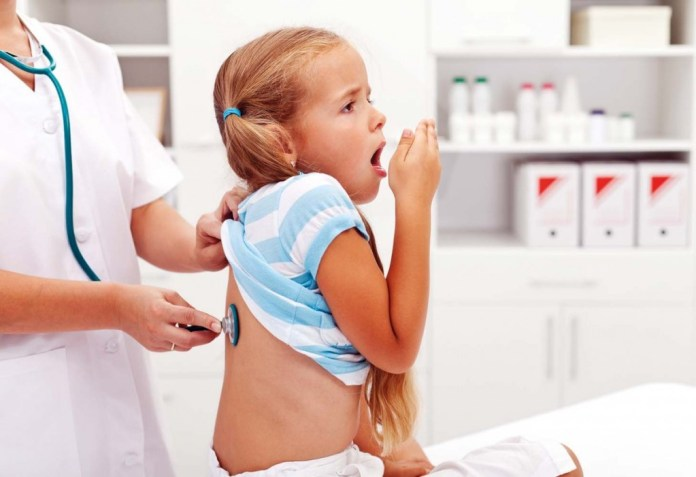 Little girl coughing at the doctor checkup - a health profession