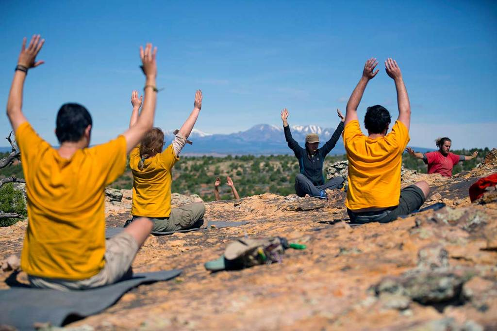 A group of Open Sky Wilderness Therapy students wearing yellow t-shirts do yoga on a rocky outcropping with mountains in the background.