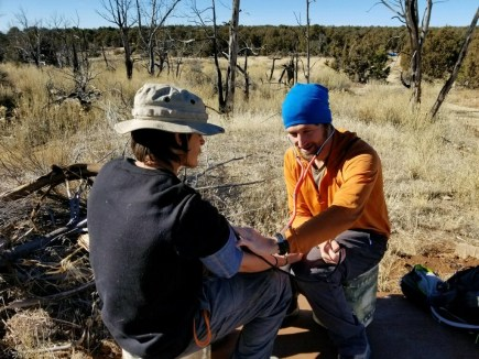 Field medic checks blood pressure. Student safety in wilderness is Open Sky's first priority.