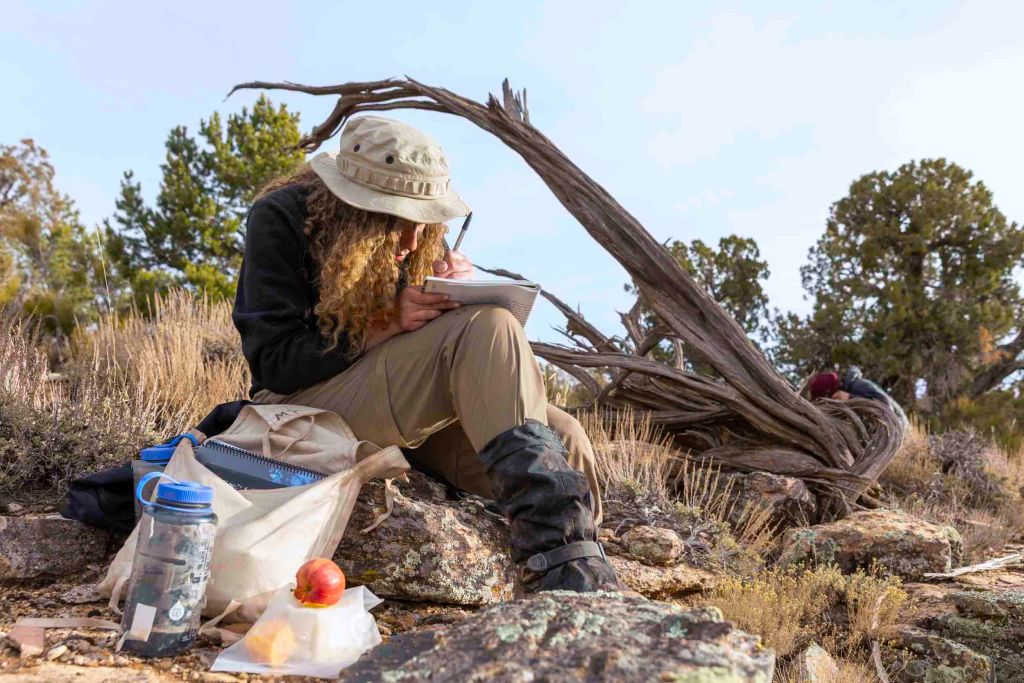 An Open Sky Wilderness Therapy student writes in their journal while sitting on a rock in Utah.