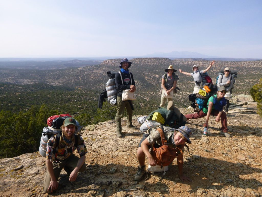 A group of Open Sky Wilderness Therapy guides pose on a rocky outcropping together.