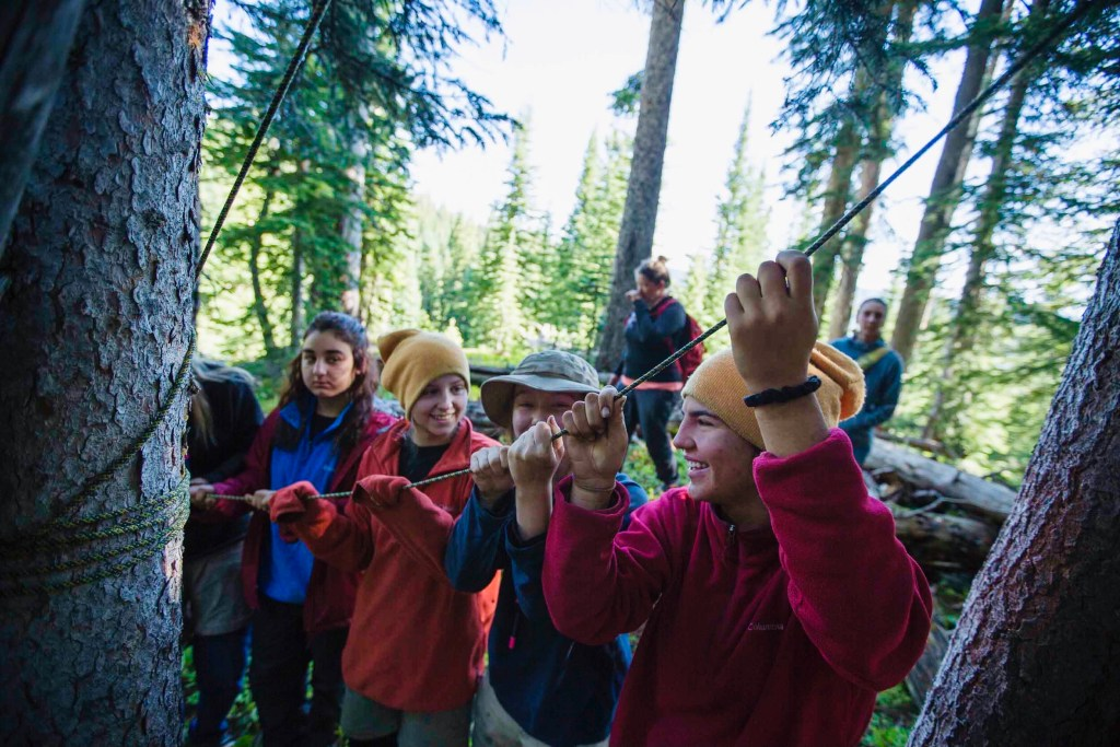 A group of adolescent students at Open Sky Wilderness Therapy work together to set a bear hang.