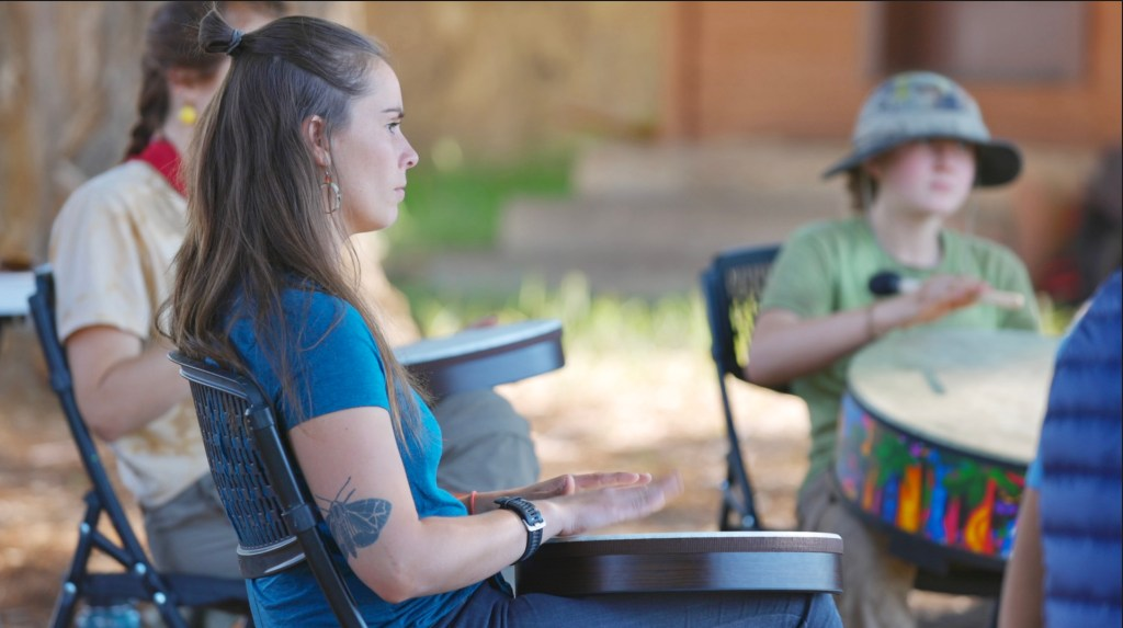 Clinical therapist Julia Lehr beats a drum with Open Sky Wilderness Therapy students at Medicine Horse Center.