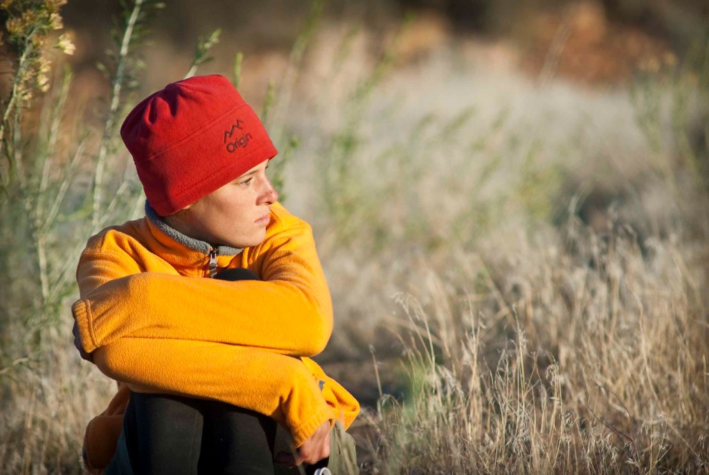 An Open Sky Wilderness Therapy student sits in a field of grass and looks off into the distance.