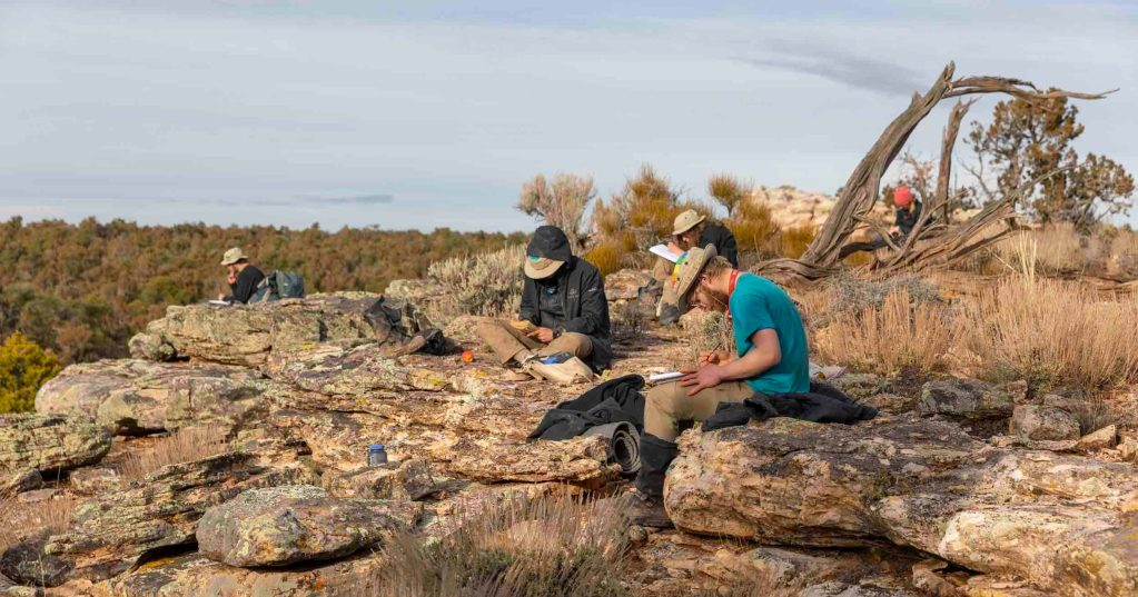 A group of students at Open Sky Wilderness Therapy sit near one another while quietly writing in notebooks.