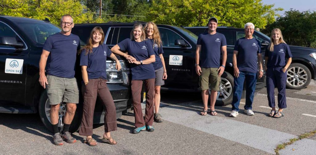Open Sky Wilderness Therapy's transportation team stands next to a fleet of vehicles while wearing blue shirts.