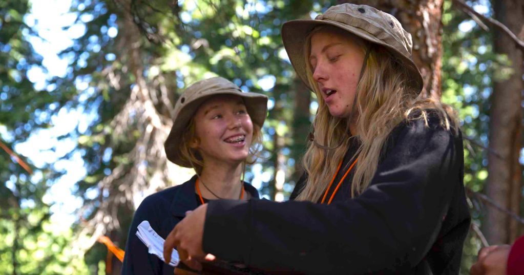 Two students at Open Sky Wilderness Therapy look at the Student Pathway together.