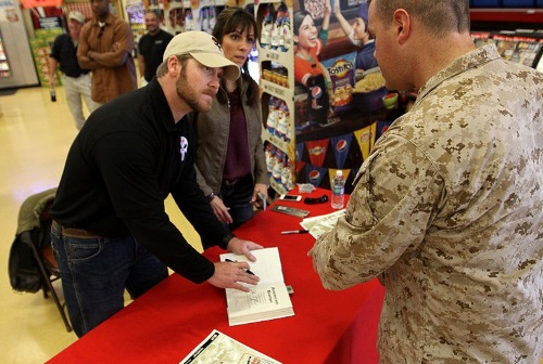 Chris Kyle signing a copy of his book - American Sniper