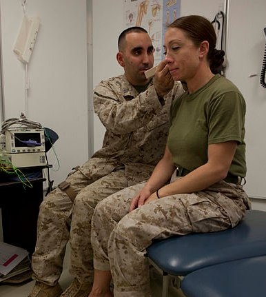 navy doctor exams a marine patient