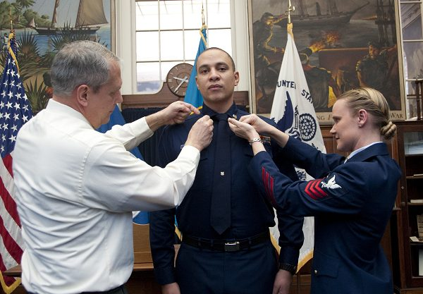 Coast Guard Servicemen pin second class crows on U.S. Coast Guard Petty Officer 2nd Class