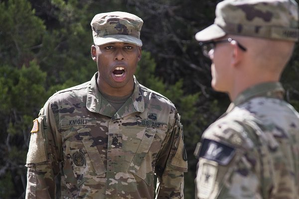 Army drill instructor gives a soldier commands on the situational training exercise lanes