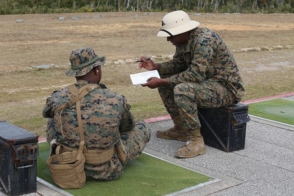 Range coach gives a Marine advice about their shot grouping to prepare for USMC rifle qualification