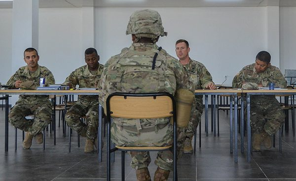 Soldiers up for promotion in the Army sit with a promotion board