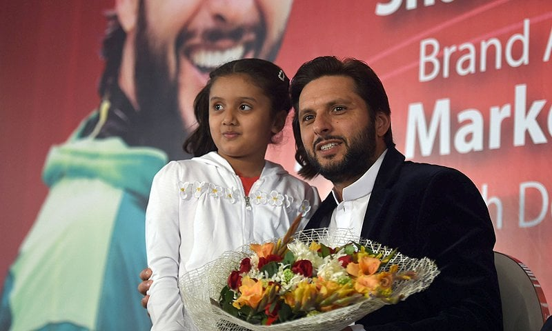 Shahid Afridi (R) receives flowers from a young supporter as he attends a local event in Karachi. AFP