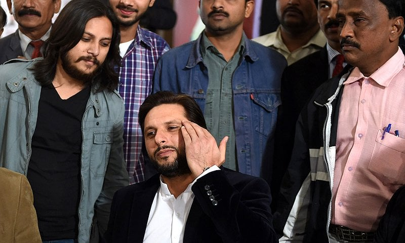 Shahid Afridi (C) posing for a photograph with his fans. AFP