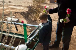 Opioid overdose funeral; father and son throwing roses into grave