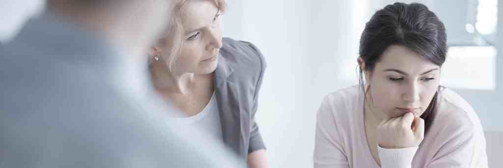 therapists talk to young woman in treatment for opioid use disorder