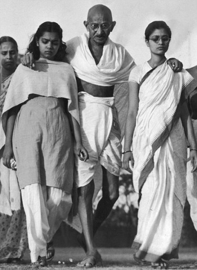 May 1946: Hindu ldr. Mohandas Gandhi (4R) walking w. (L-R) his secretaries Shushila Pai, Raj Kumari, his son Manilal, his secy. Pyarelal, his son's wife, his granddaughter Sita, his nephew's wife Abha, & two unident. men, on his daily walk around his colony.  (Photo by Margaret Bourke-White/Time & Life Pictures/Getty Images)