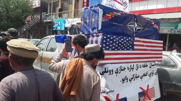 Taliban holds mock funeral with coffins wrapped in US and NATO flags after end of Afghanistan War