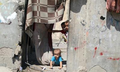 A Palestinian child crawls as other children look out of their family house in Al Shati refugee camp in Gaza City