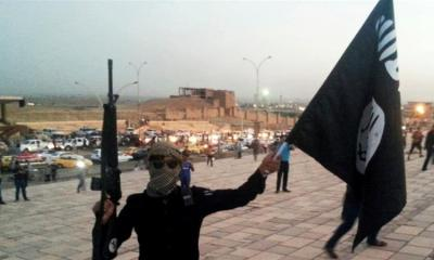 A fighter of the Islamic State of Iraq and the Levant holds an black flag and a weapon on a street in the city of Mosul Iraq